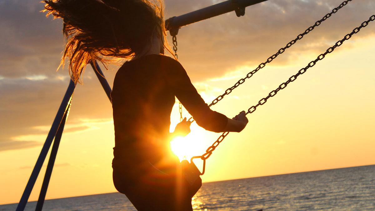 ragazza su altalena al tramonto vicino al mare