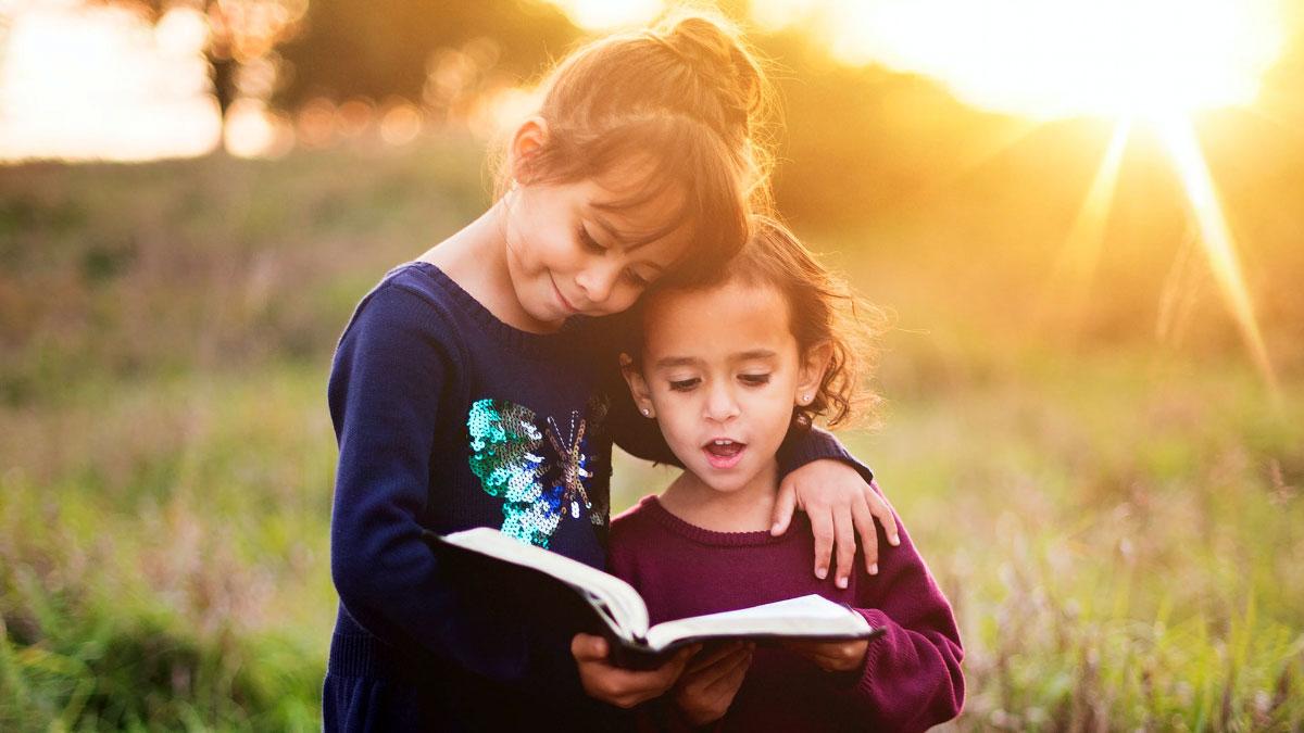 bambine abbracciate leggono un libro