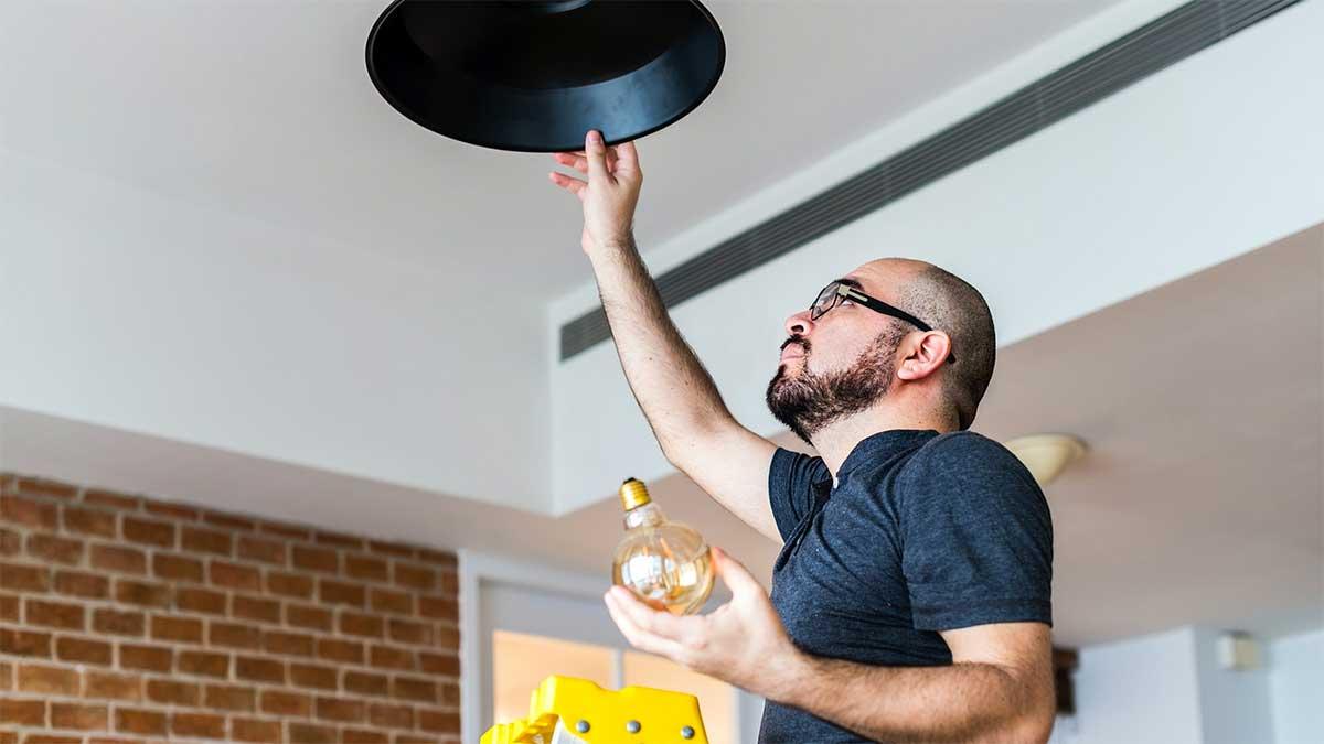 uomo che cambia lampadina al lampadario