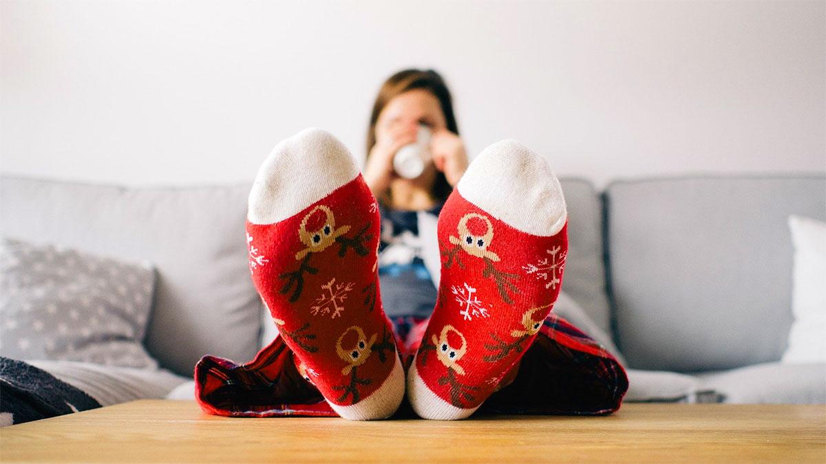 ragazza sul divano con i calzini di Natale
