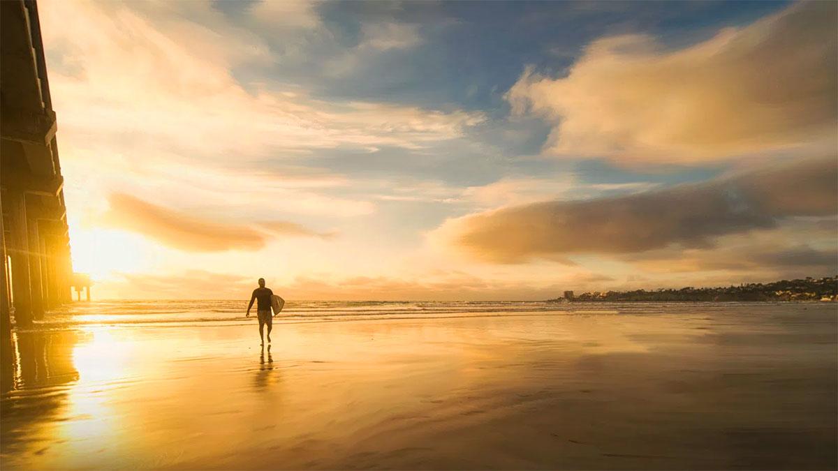 Uomo all'alba che si appresta a fare surf
