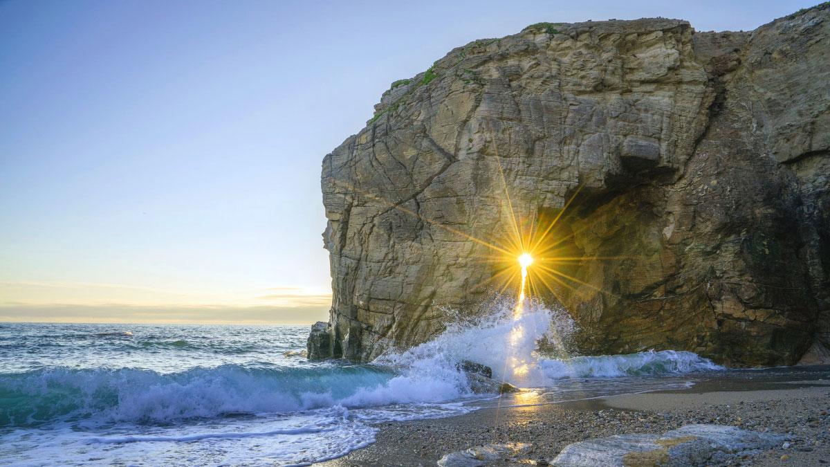 mare con il sole che filtra dalla roccia