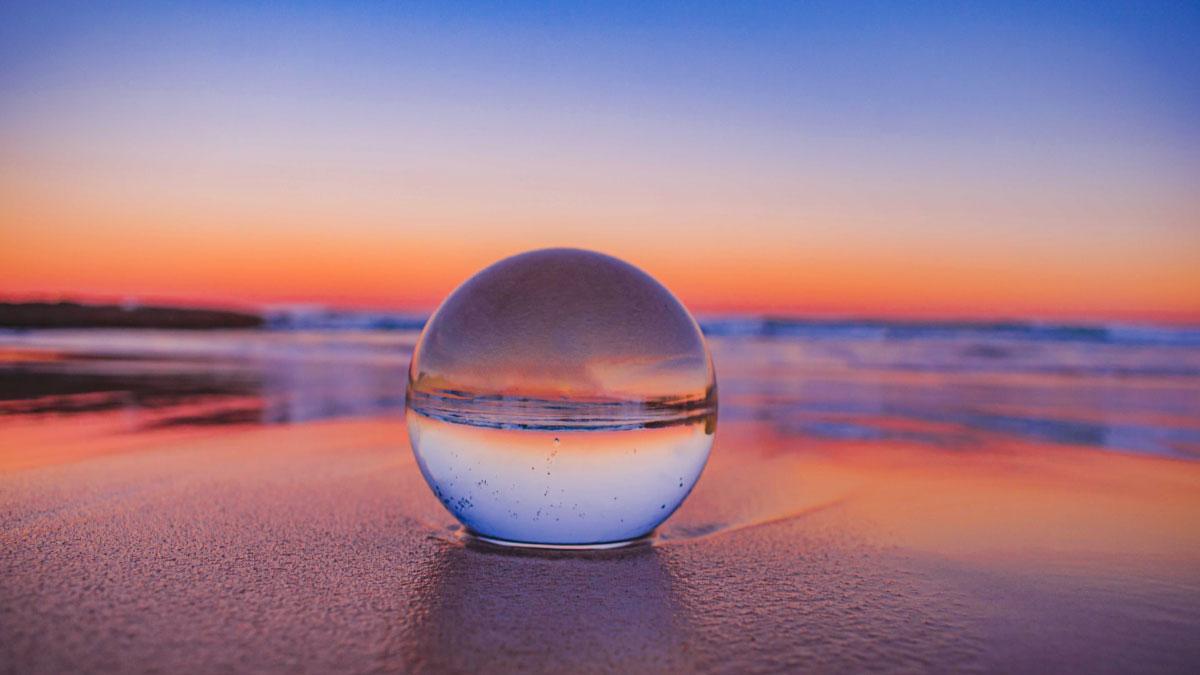 palla di vetro sulla sabbia con il mare all'orizzonte