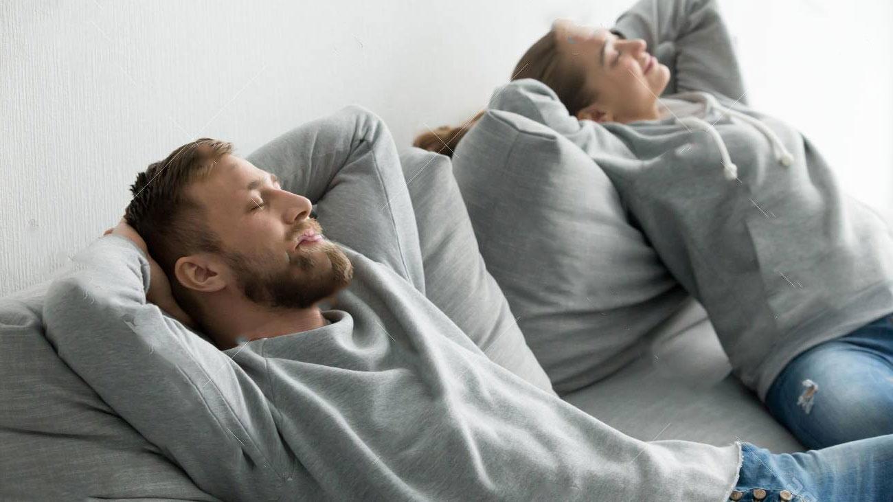 Coppia che pensa felice seduta su un divano grigio