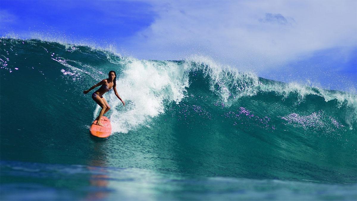 ragazza che fa surf su un'onda alta