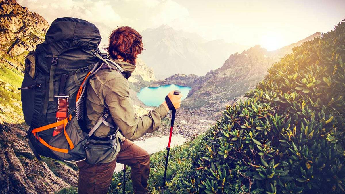 ragazzo con lo zaino in montagna che ammira il paesaggio